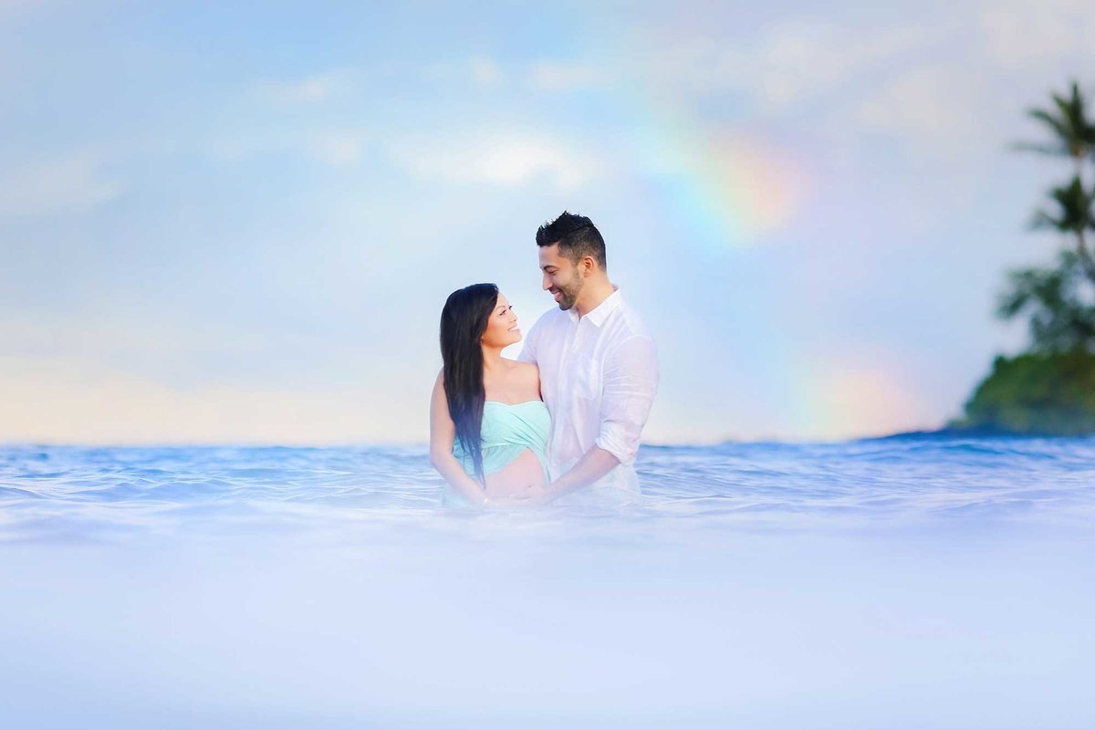 Pregnant woman and man in the ocean on Maui with rainbow in the background