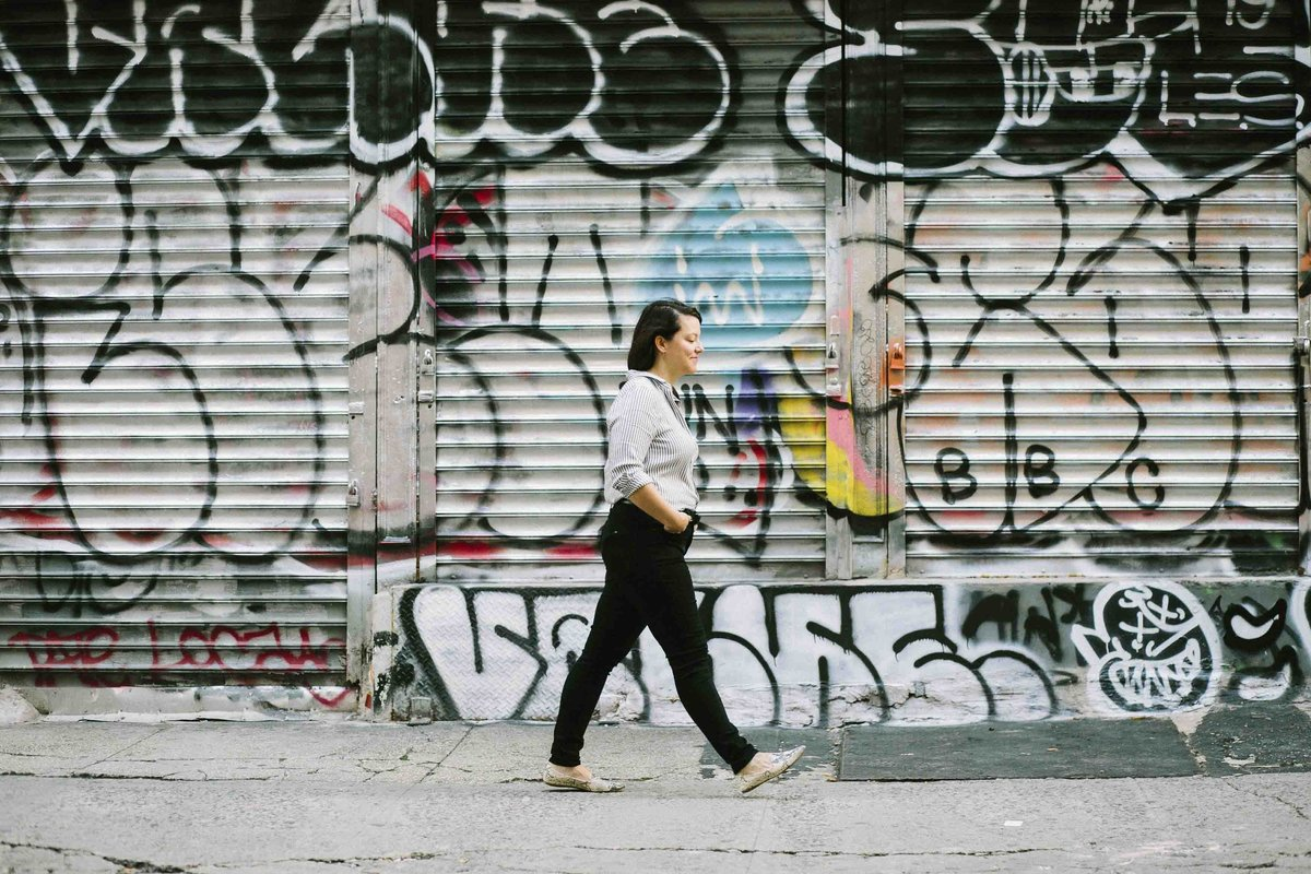 Women walking in front graffiti wall of