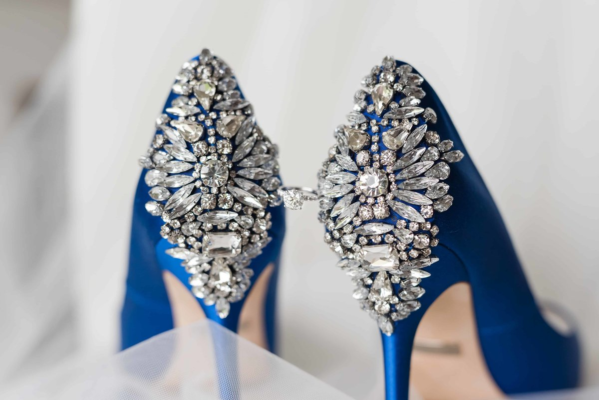 Sparkly wedding shoes holding engagement ring.