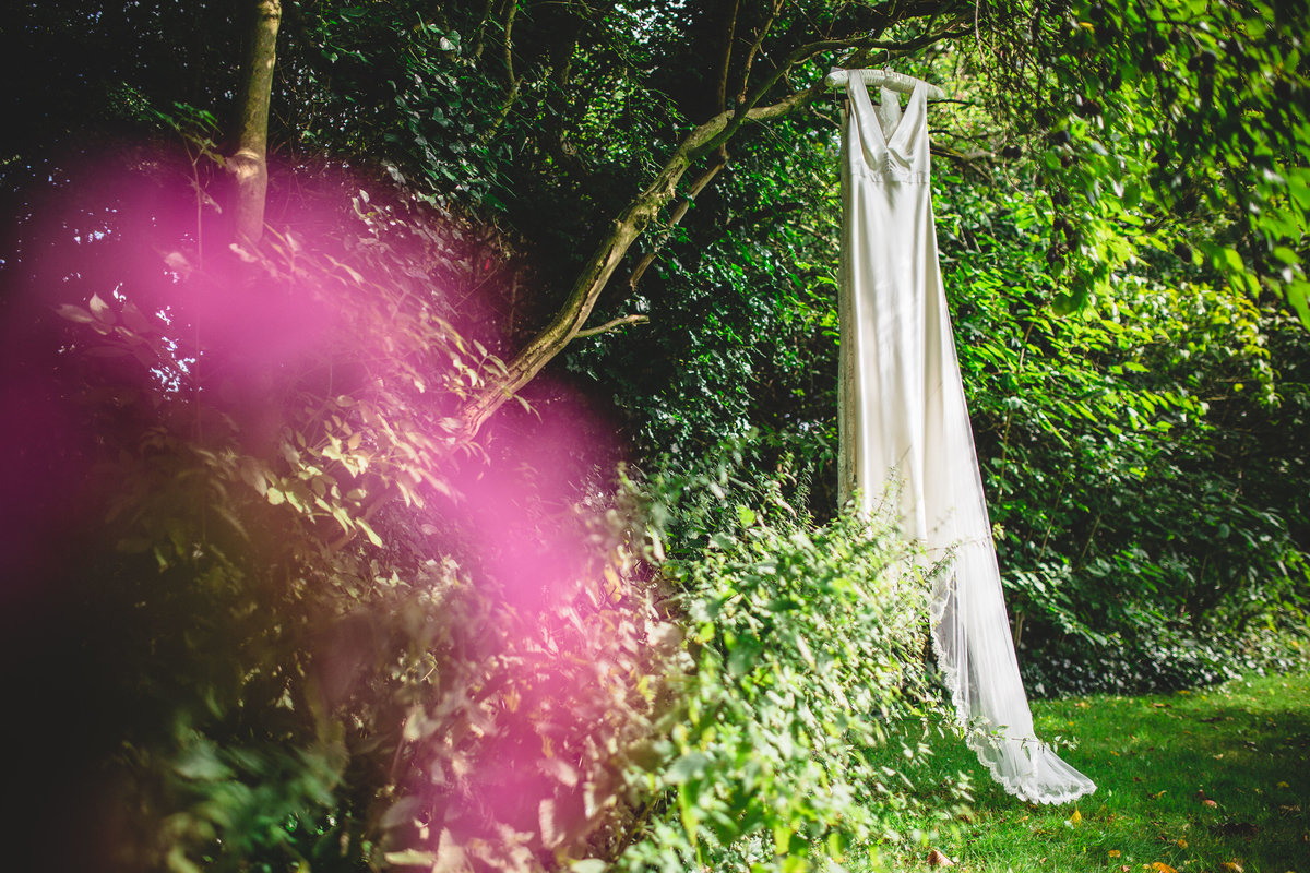 a silk wedding dress hanging in a tree