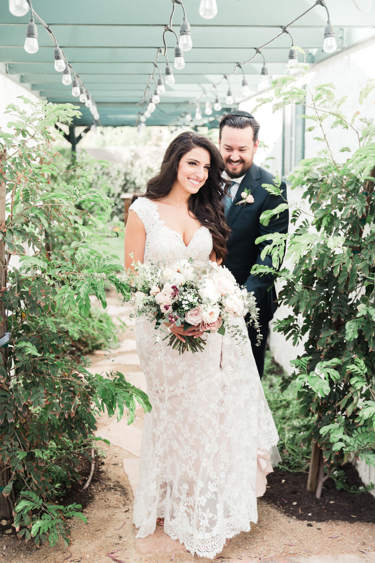 a photo of a bride and groom in their backyard wedding in Las Vegas with a lace dress and a lush floral bridal bouquet