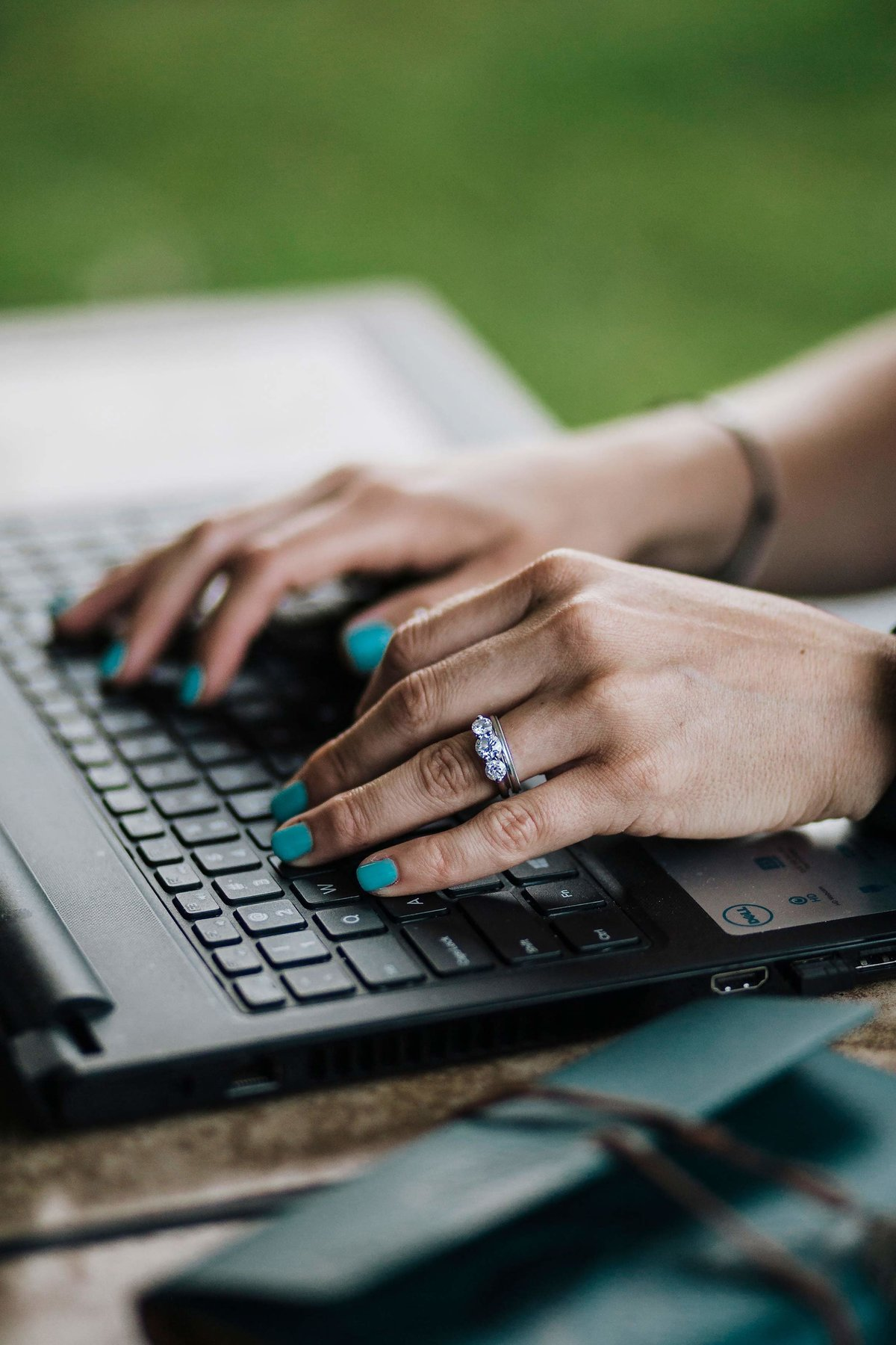 A woman's hands typing on a laptop.
