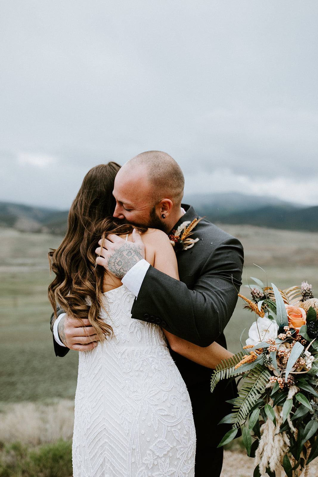 A bride and groom embrace in a field.