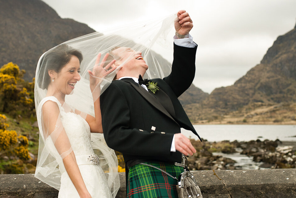 brunette bride wearing an a-line wedding dress with capped sleeves with her husband wearing a scottish kilt wedding suit, pulling the bride's veil off his head while standing on a stone bridge at the Gap of Dunloe