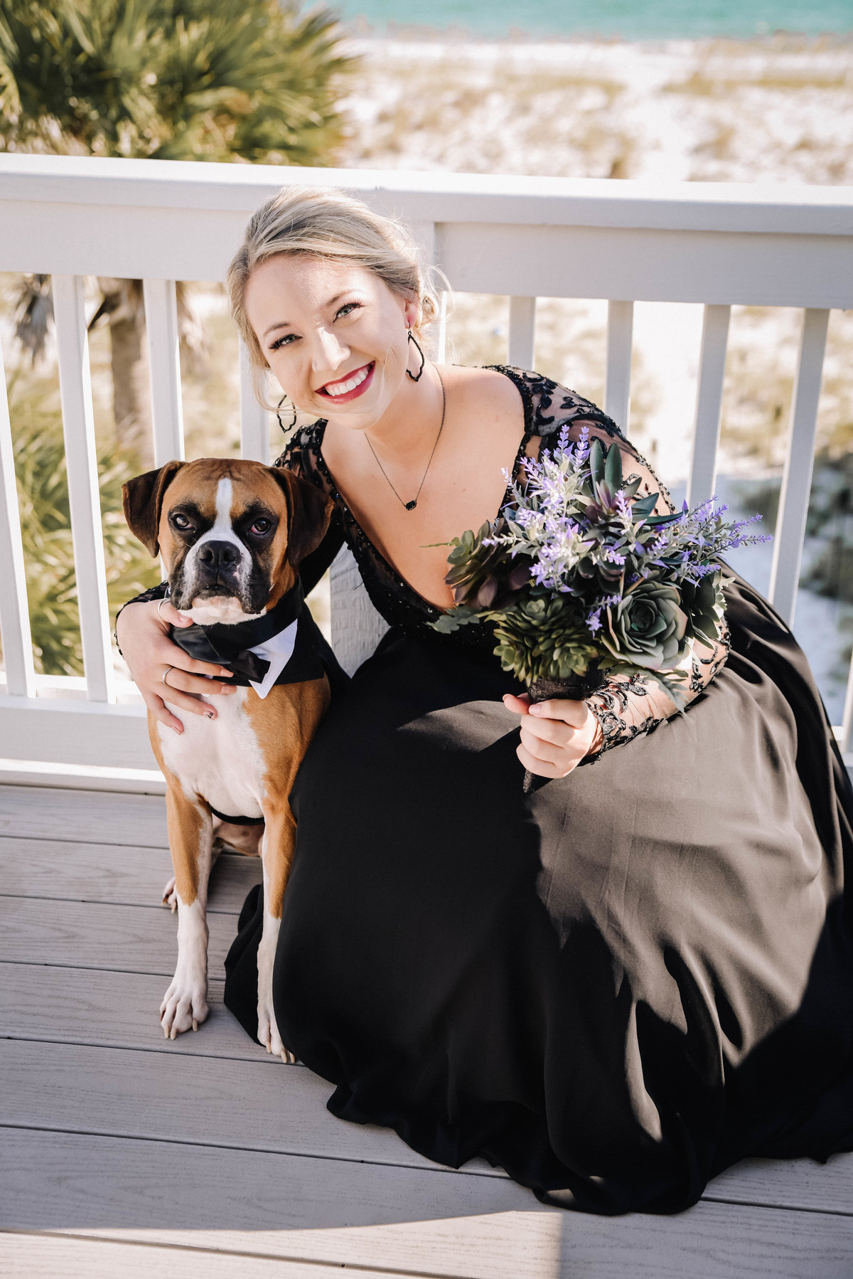 Bride in black wedding dress kneeling down hugging her dog  on her wedding day in Pensacola, FL