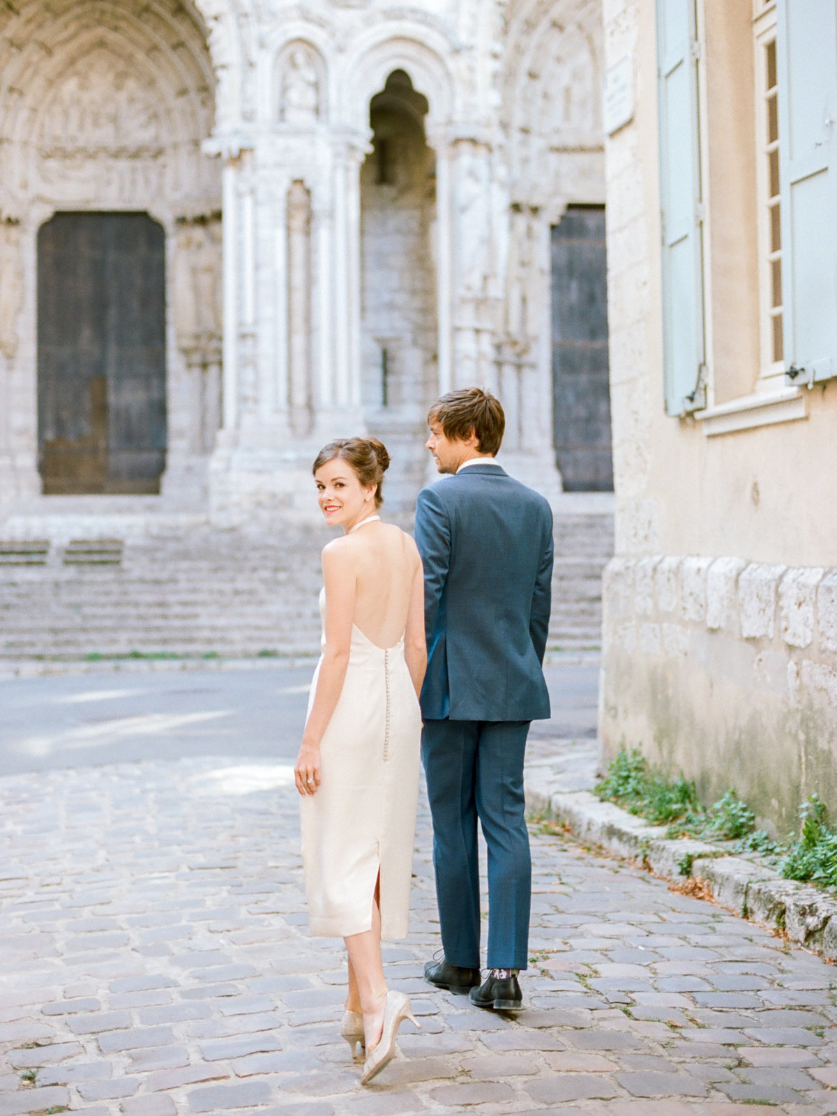 couple walking down cobblestone street in france