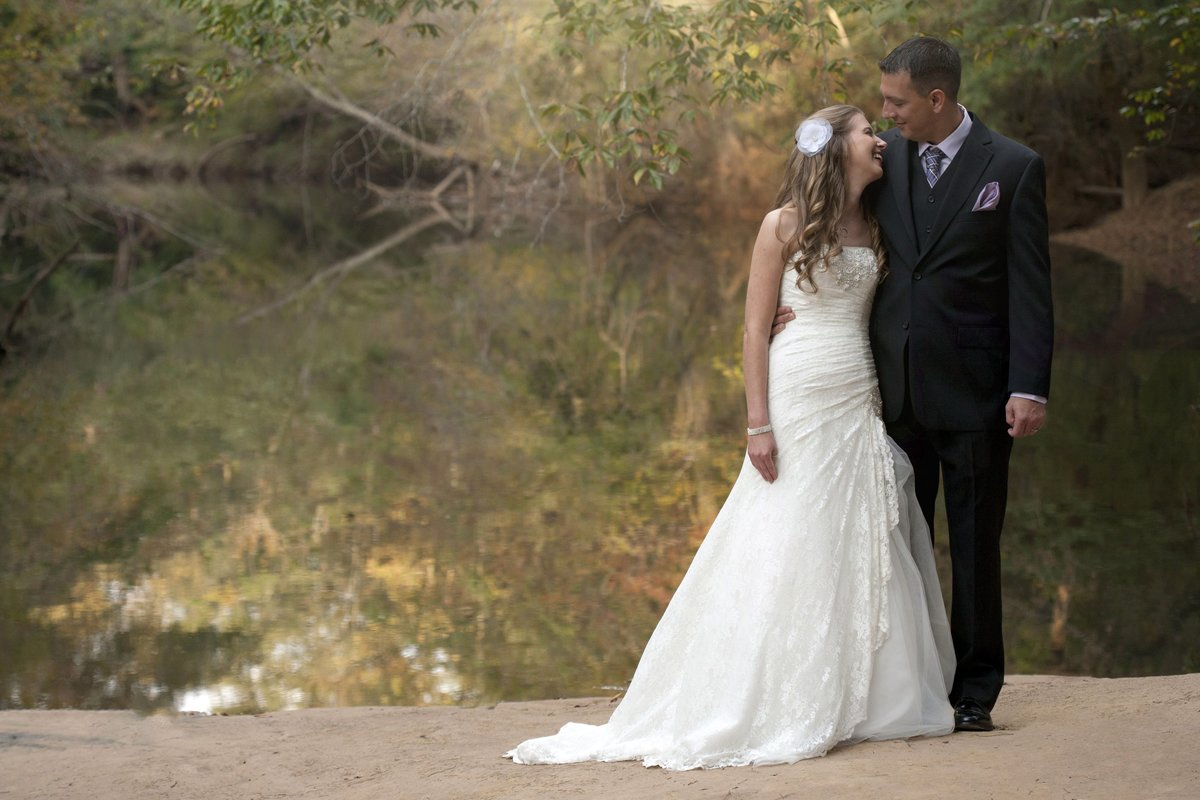 bride and groom laughing at lake