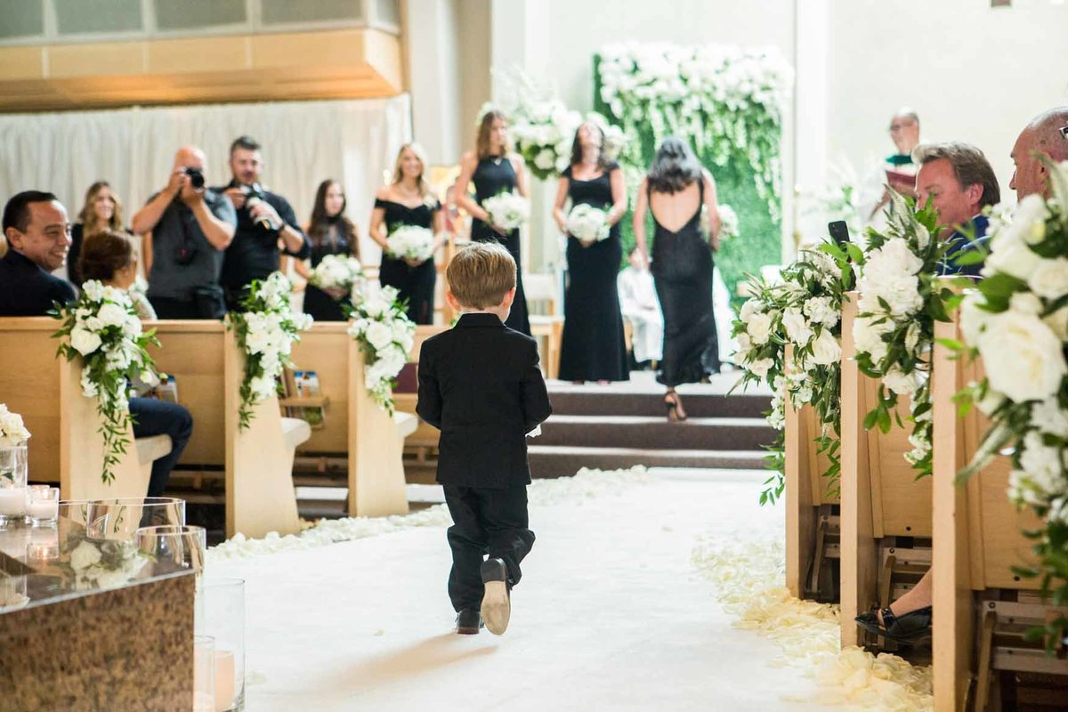 Ring bearer walks up aisle with white rose petals