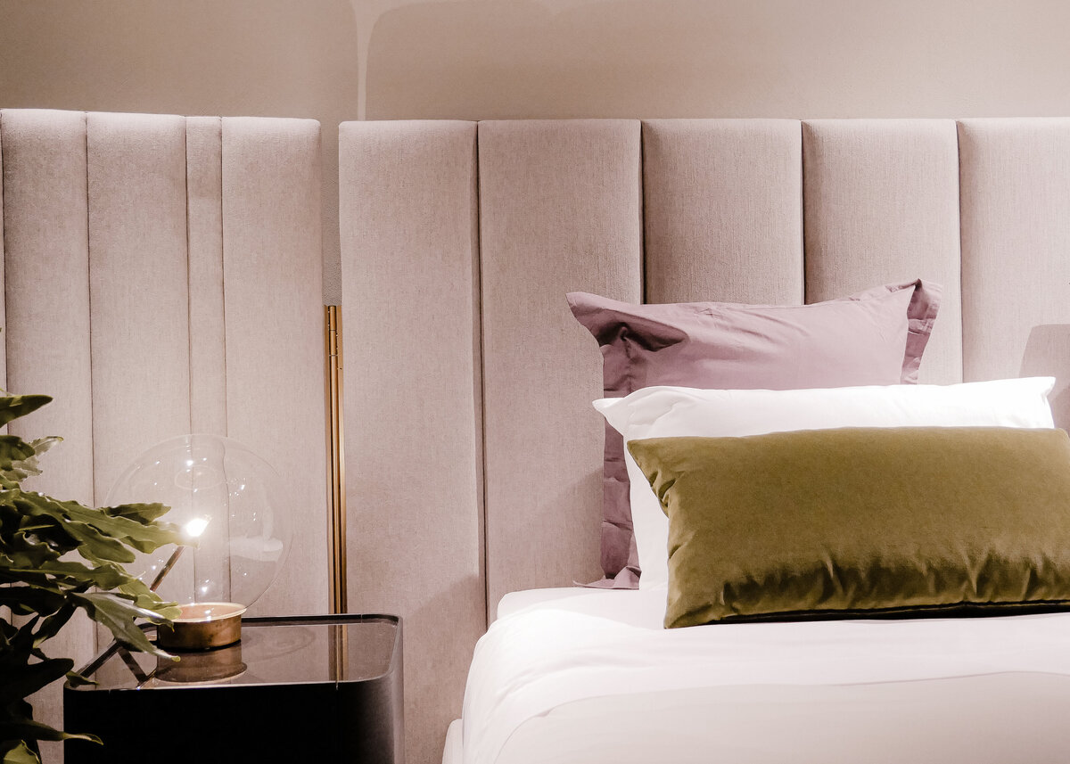 A padded pink headboard is styled with a moss green velvet pillow on a white duvet.