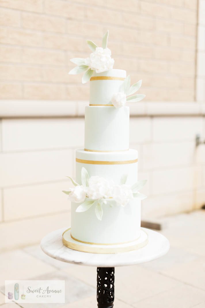 modern french blue wedding cake with gold accents and white flowers