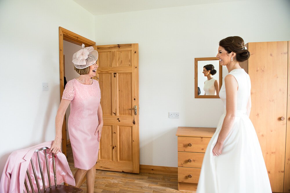 mother of the bride wearing pink and a birdcage headpiece looking at her daughter, wearing a vintage, tea length wedding dress