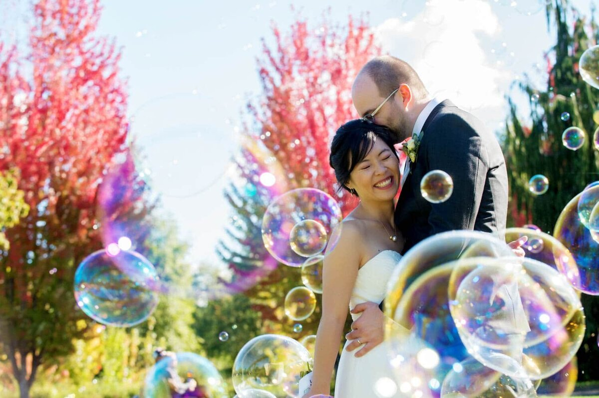 colorful photo of bride and groom hugging with rainbow bubbles surrounding them