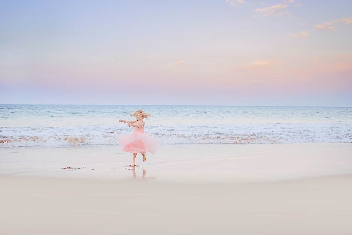 Girl in pink dress twirls on the beach on Maui during a sunrise family portrait session