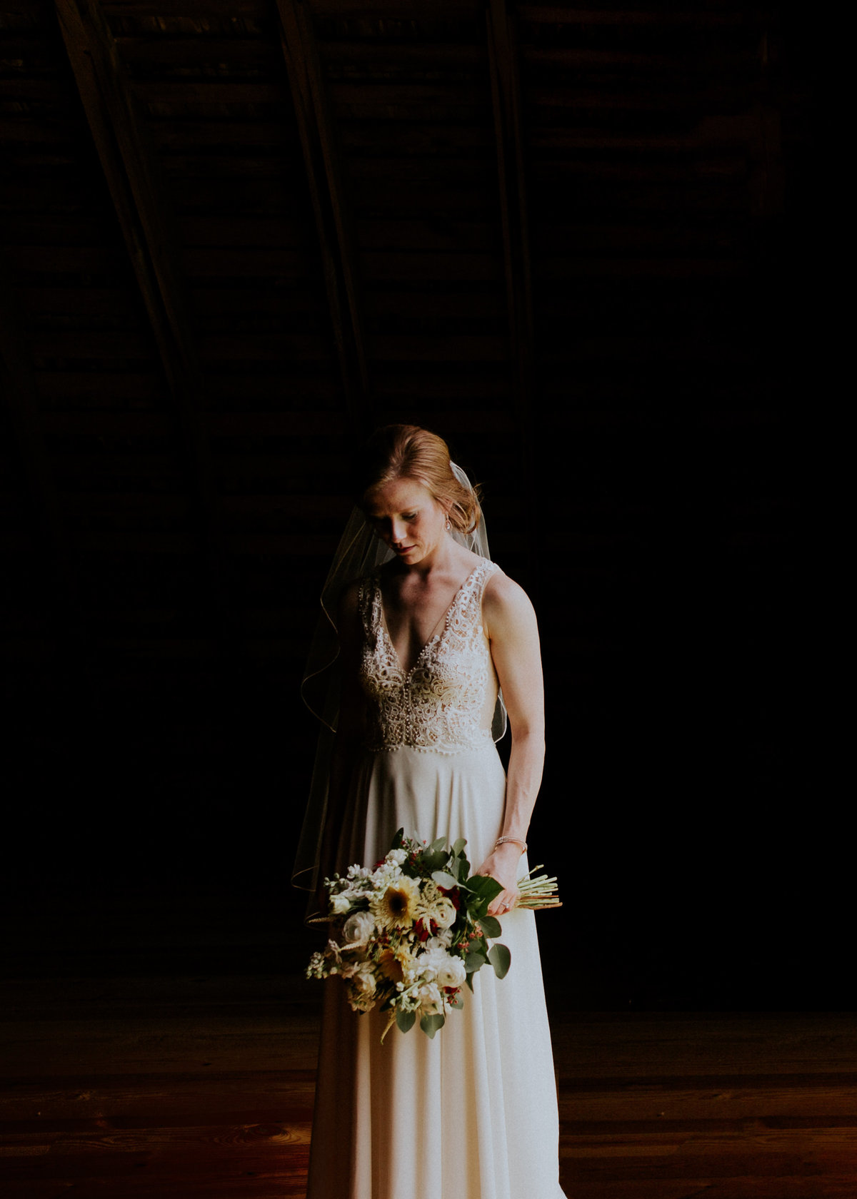 A bride and her bouquet in a barn