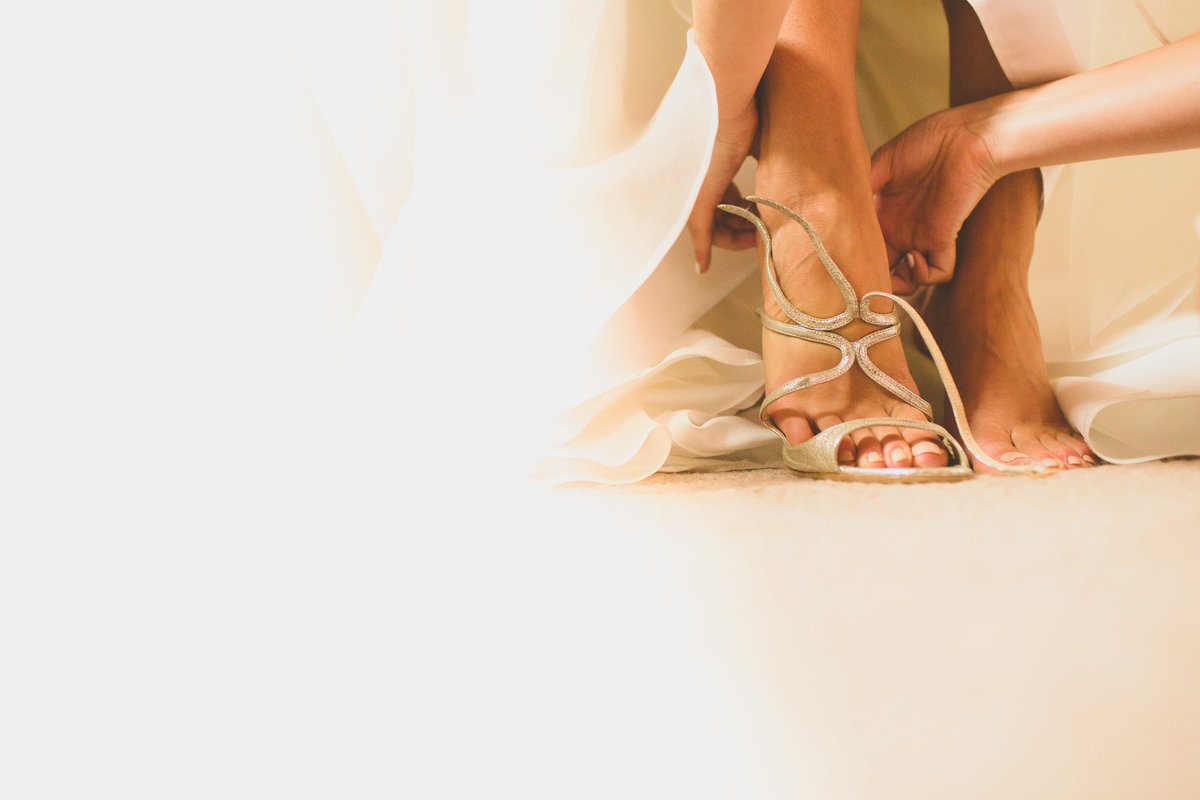 closeup photograph of bride putting jimmy choo wedding shoes on