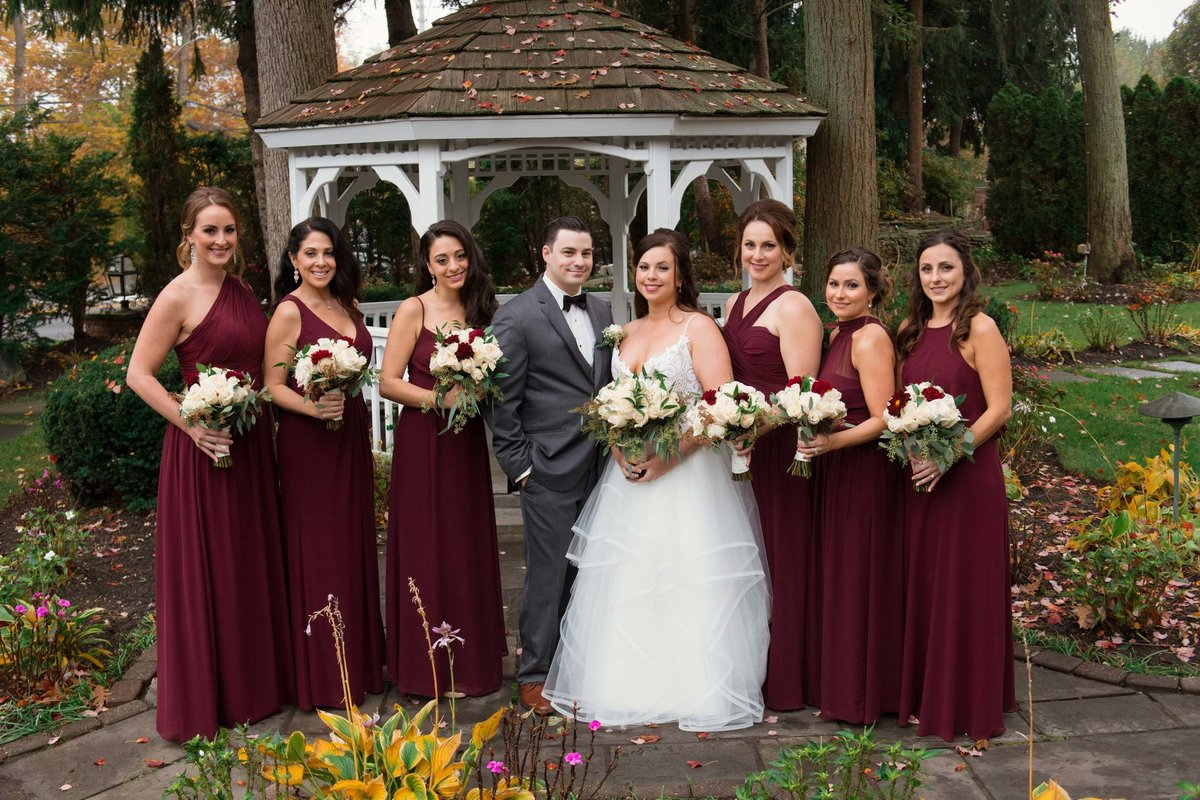Bridesmaids in red dresses at Fox Hollow