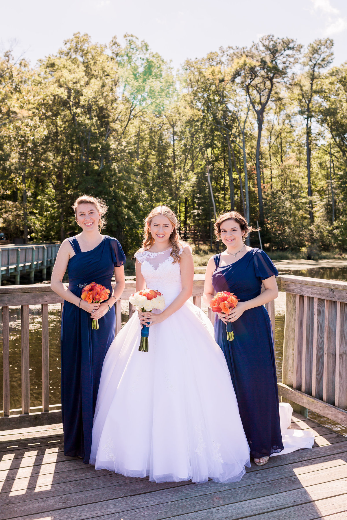 A bride and her bridesmaids pose on the boardwalk at Newport News Park