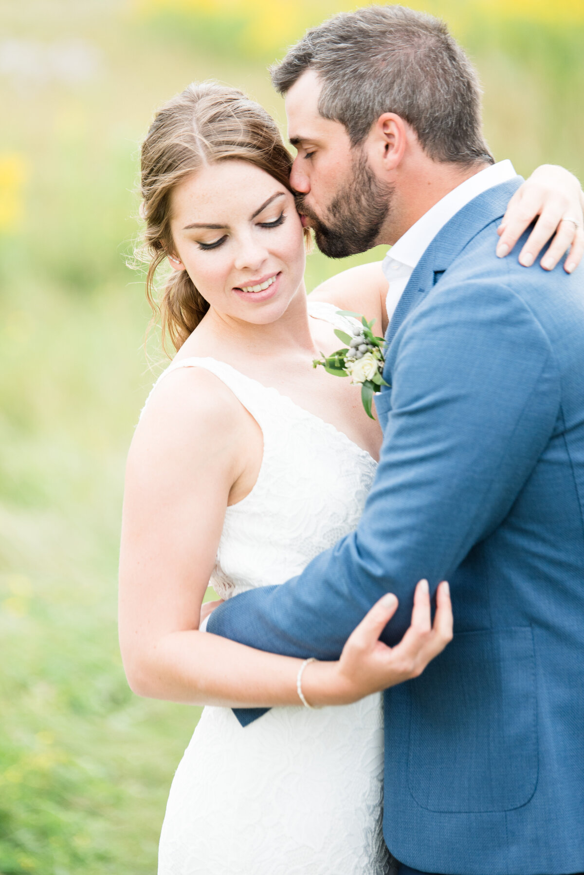 A groom nuzzles in to his bride during portraits at their Norwester Thunder Bay Wedding