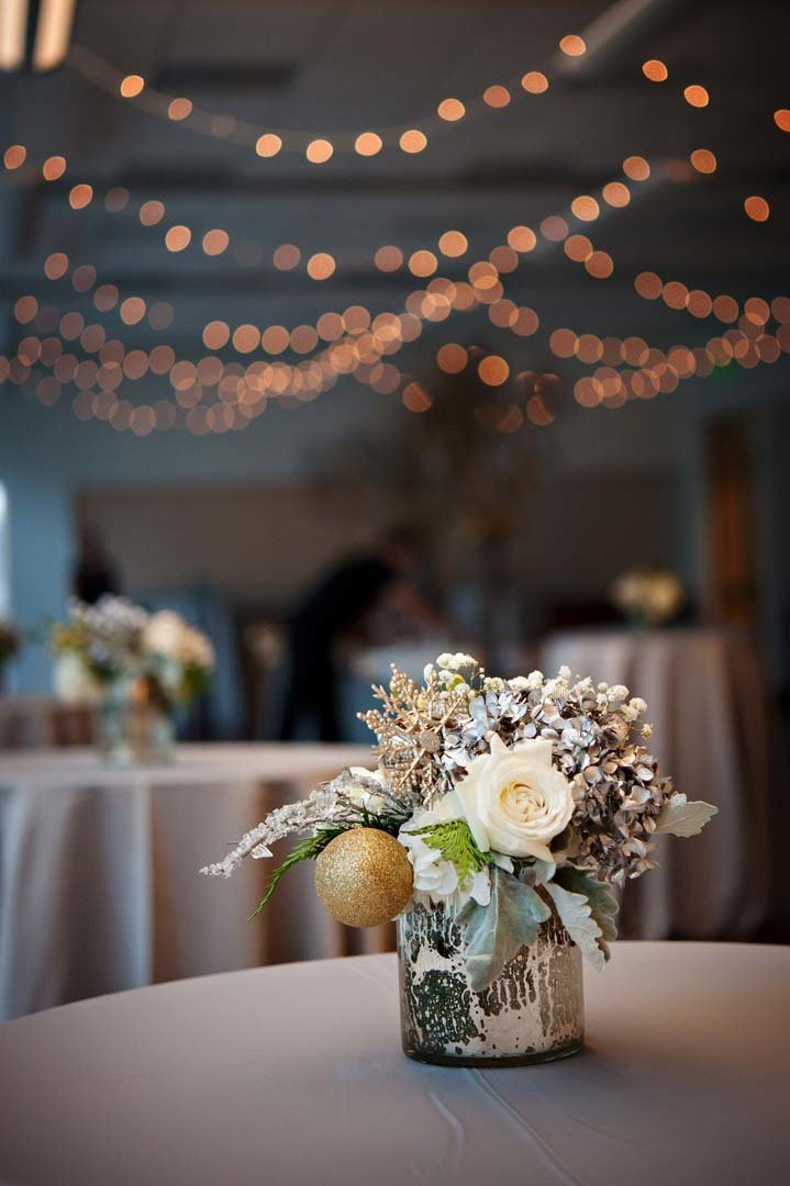 corporate holiday party decor ideas with white flower centerpiece in silver vase on silver table linen