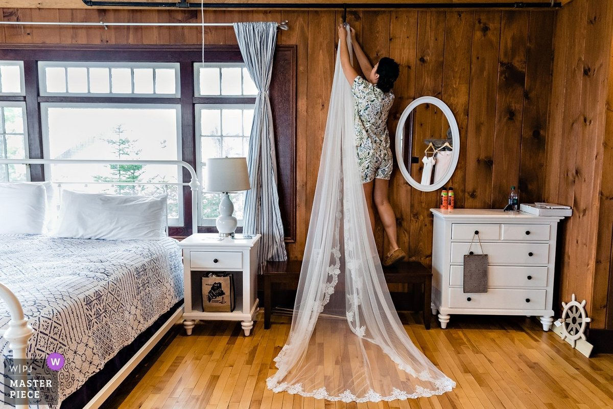 Linekin Bay Resort Wedding the bridesmaid hangs the cathedral length veil in the cabin in Boothbay Harbor Maine