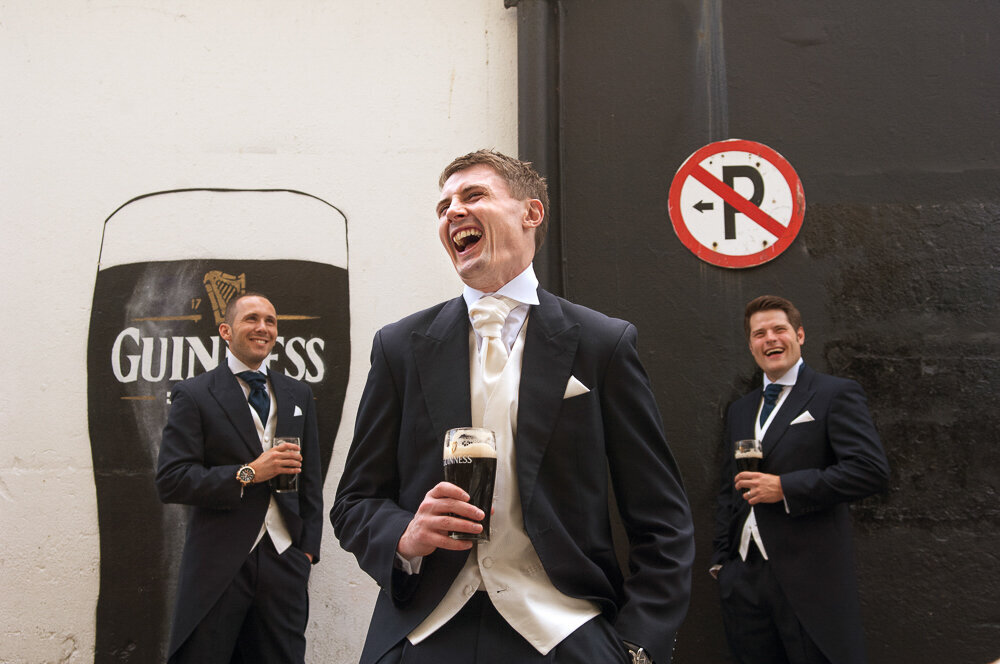 Groom and his groomsmen wearing black tailcoats and cream cravat laughing and holding pints of Guinness