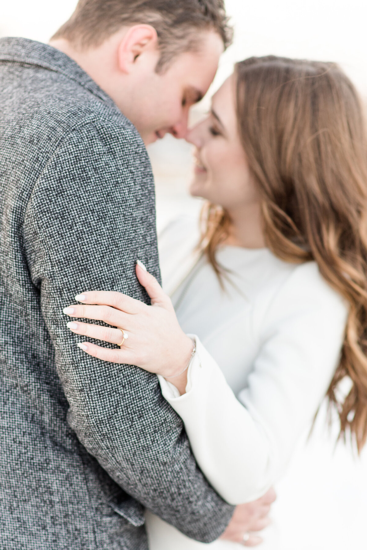 A couple cuddles in close during their winter engagement session in Thunder Bay