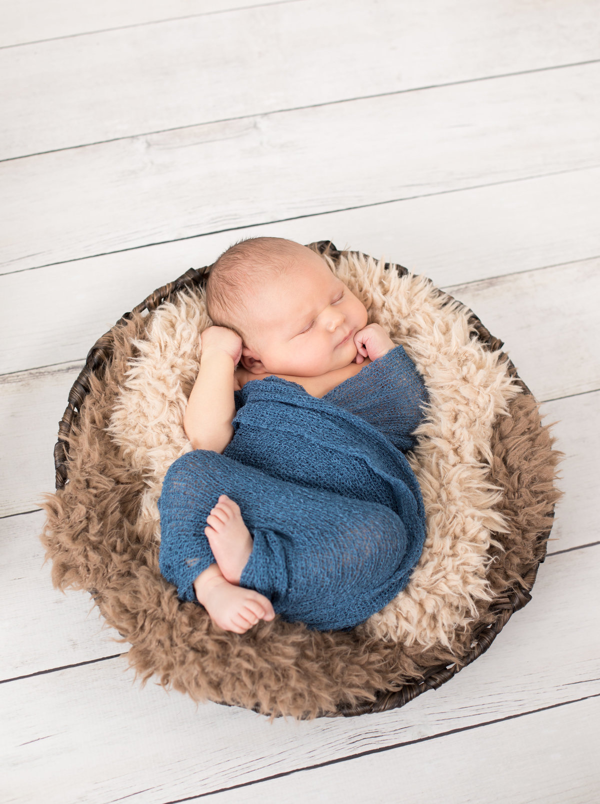 Newborn boy in blue wrap on a furry blanket in a round dark brown basket on a white wood floor