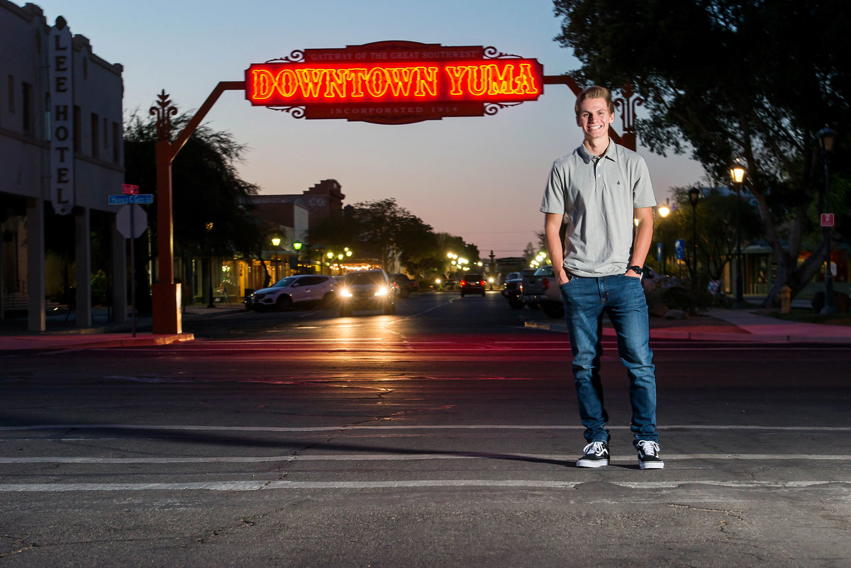 senior with Downtown Yuma sign at night