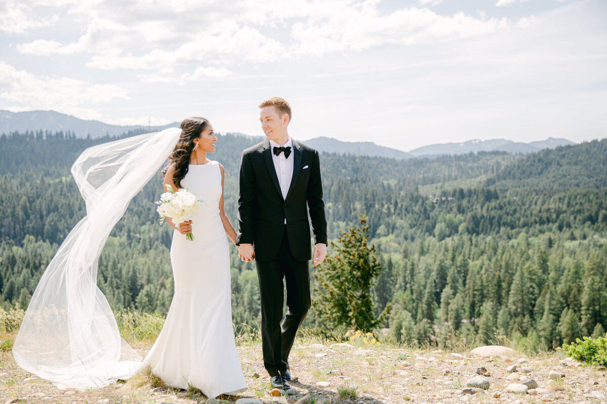 Bride with her veil blowing holding hands with Groom walking with  mountains in the background on a sunny day