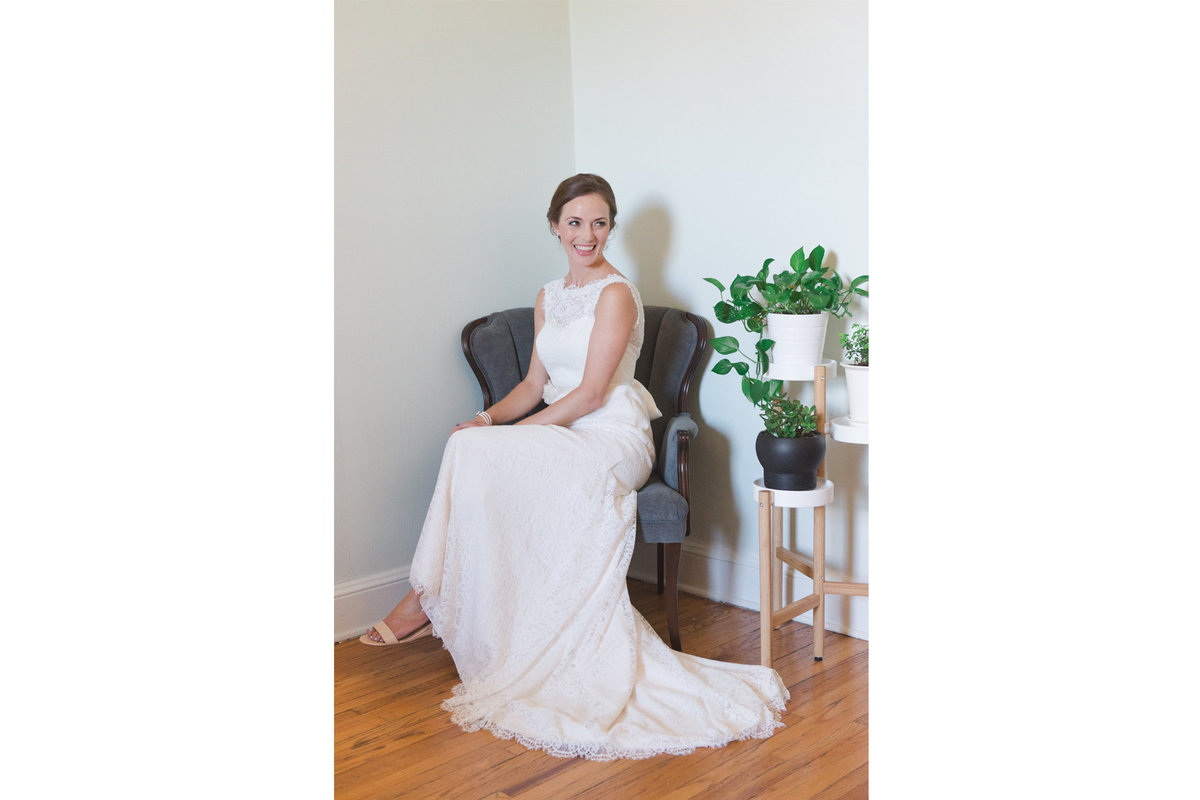 Bride sitting in vintage chair with green plants
