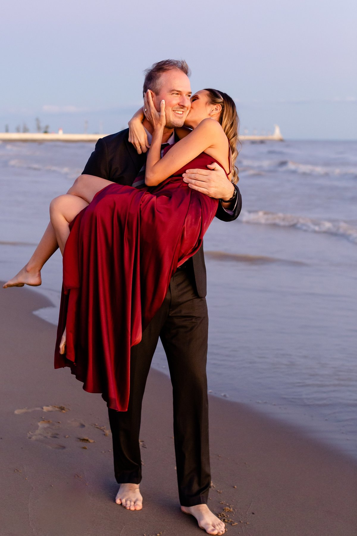 Handsome-guy-carries-his-future-wife-wearing-a-fancy-red-dress-on-port-stanley-beach-during-their-sunset-engagement-session