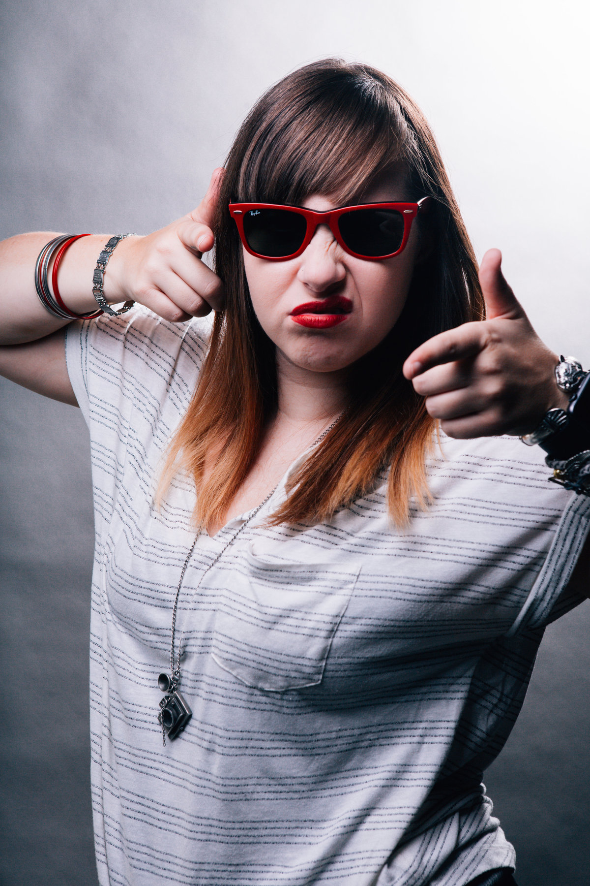 Girl poses and makes finger guns toward the camera