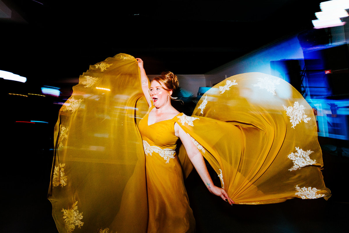 One of the top wedding photos of 2019. Taken by Adore Wedding Photography- Toledo Ohio Wedding Photographers. This photo is of bride dancing in her custom yellow wedding gown.