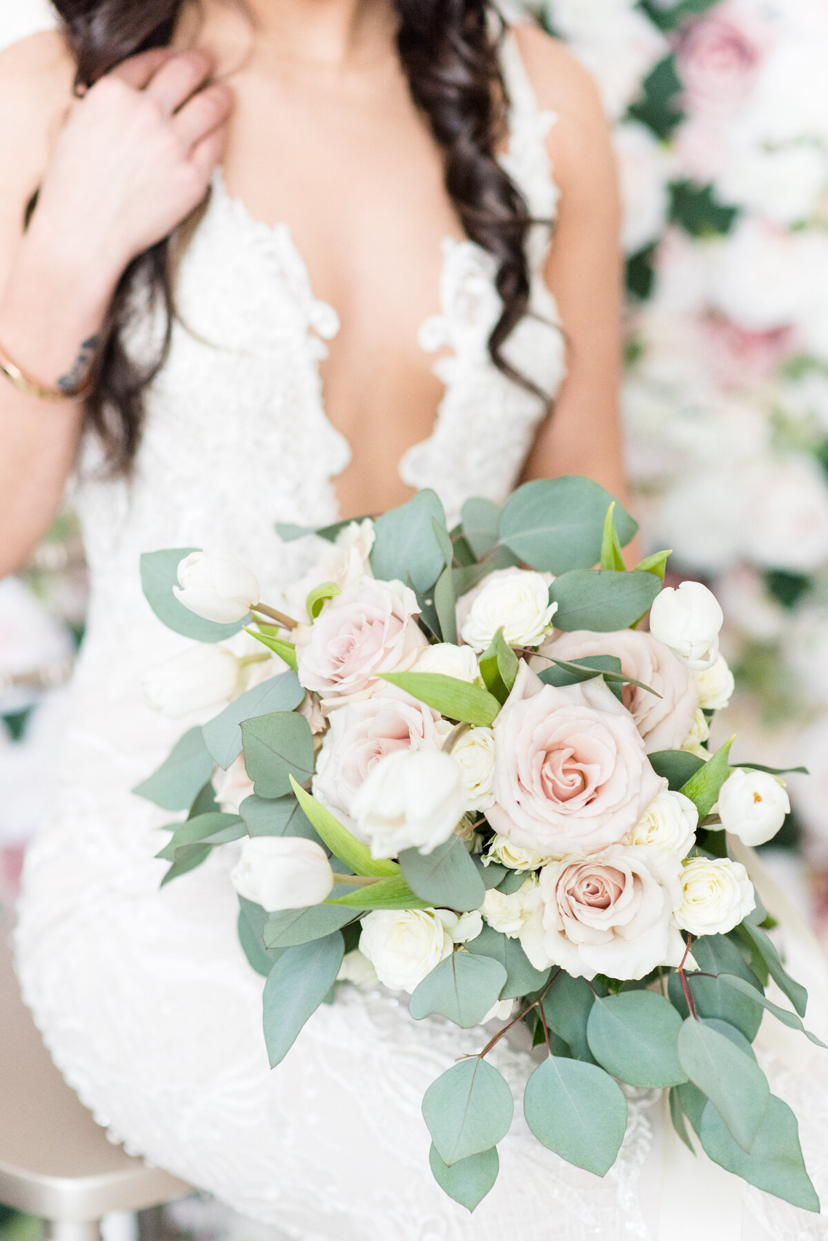A beautiful bouquet of pink roses and white tulips by Thuja Floral Design rests on the lap of a bride sitting on the champagne chiavari chairs from Luxy Chair