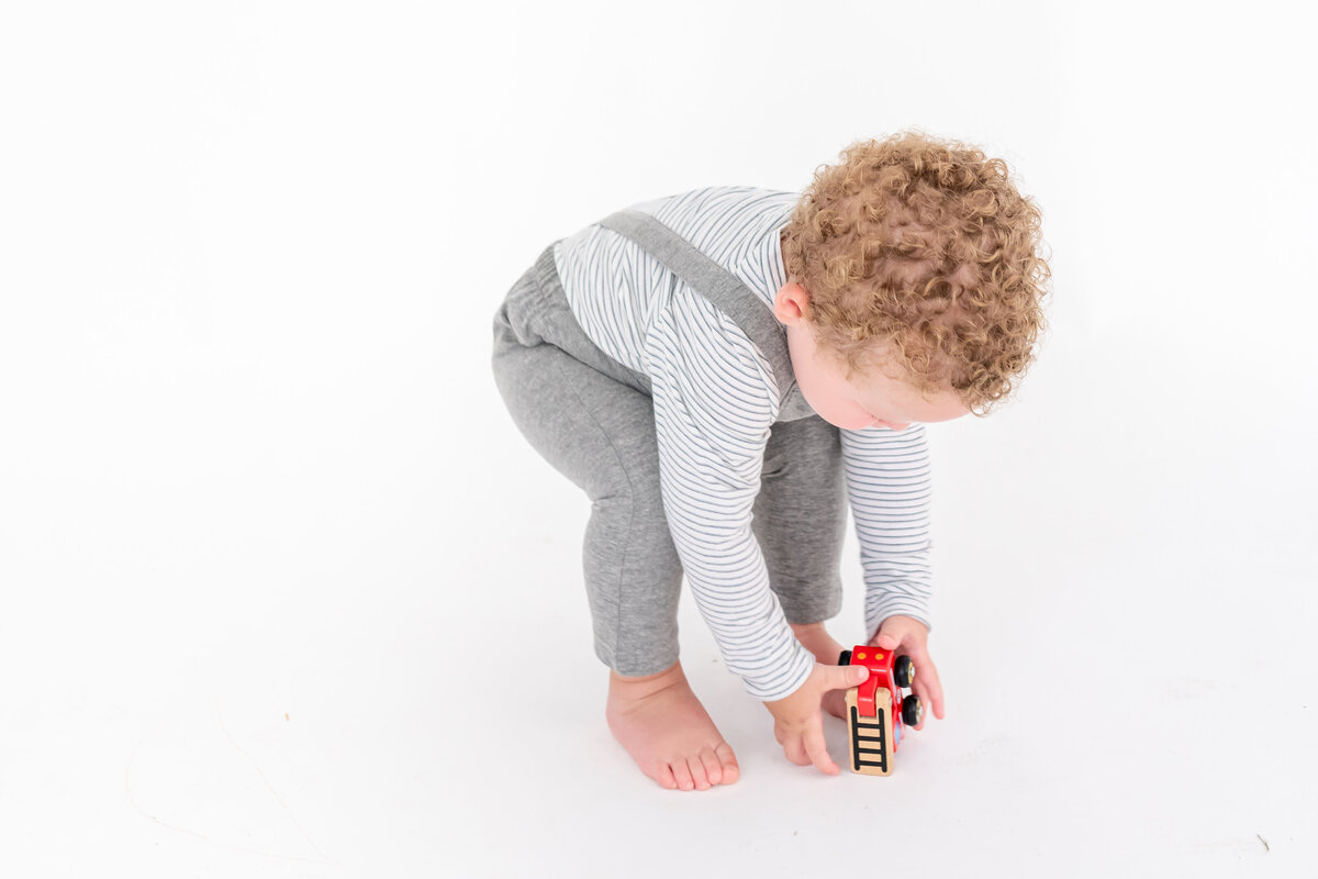 Toddler wearing a knitted romper and playing with a toy