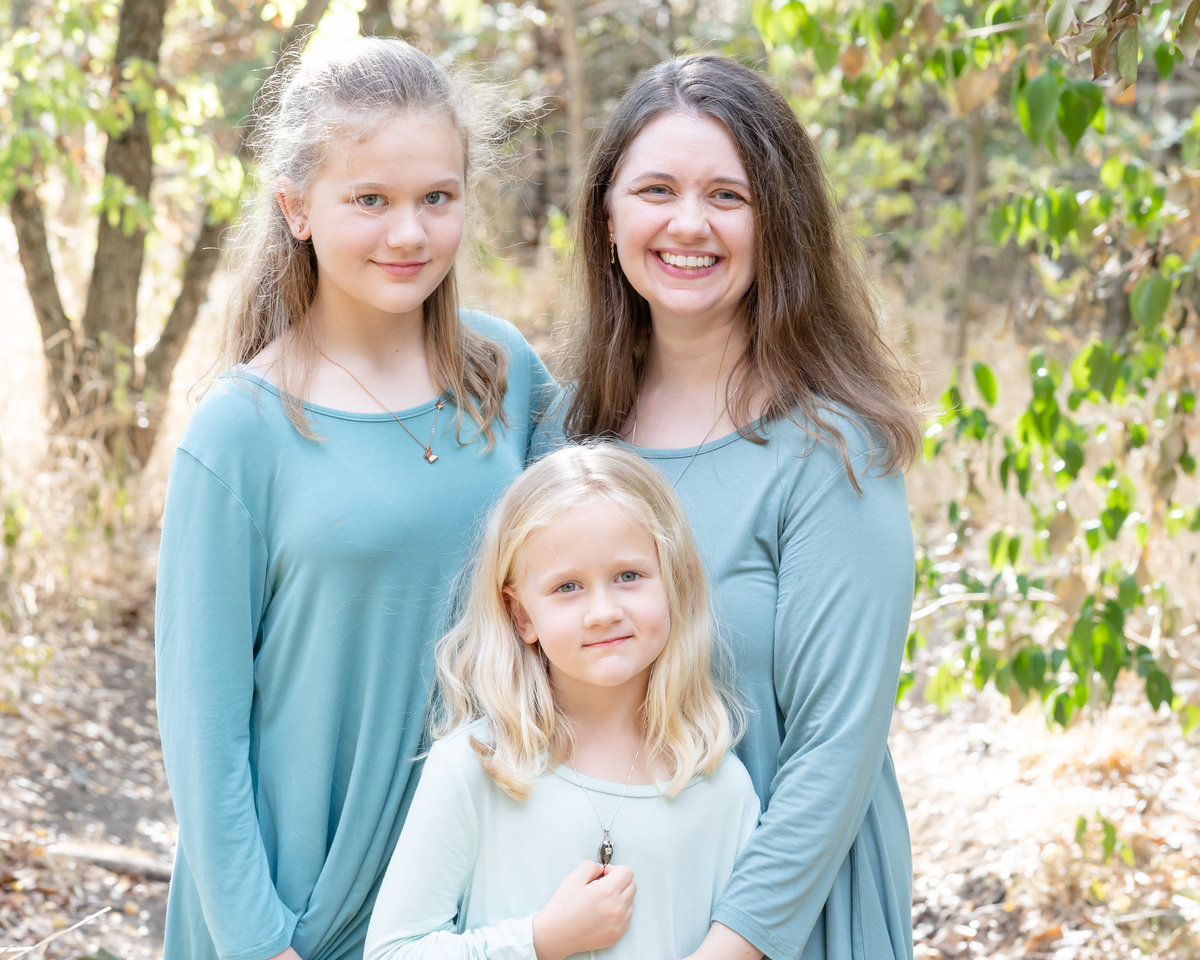 Mom and two daughters. Dressed in turquoise long sleeved shirts