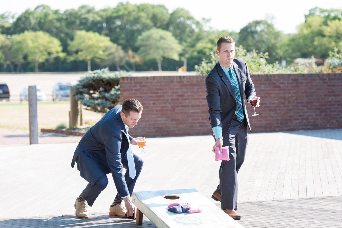 photo of groomsen playing bag toss during beach wedding reception at Pavilion at Sunken Meadow