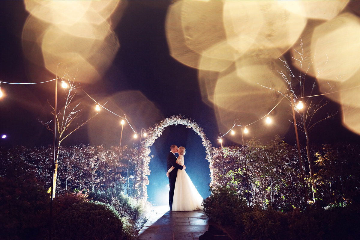 Night time fairy light portrait of a bride and groom at Owen House Barn Wedding Venue