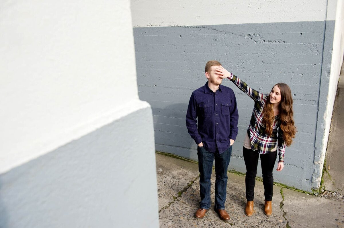 a fun and silly couple stands in front of a gray and white wall and cover each others eyes