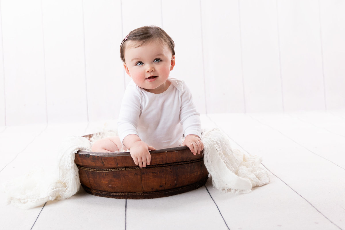 Little baby girl in a bowl with white