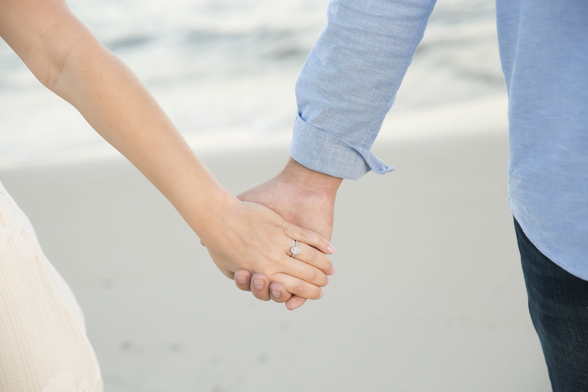 couple holds hands with engagement ring as focus and biloxi beach in the background