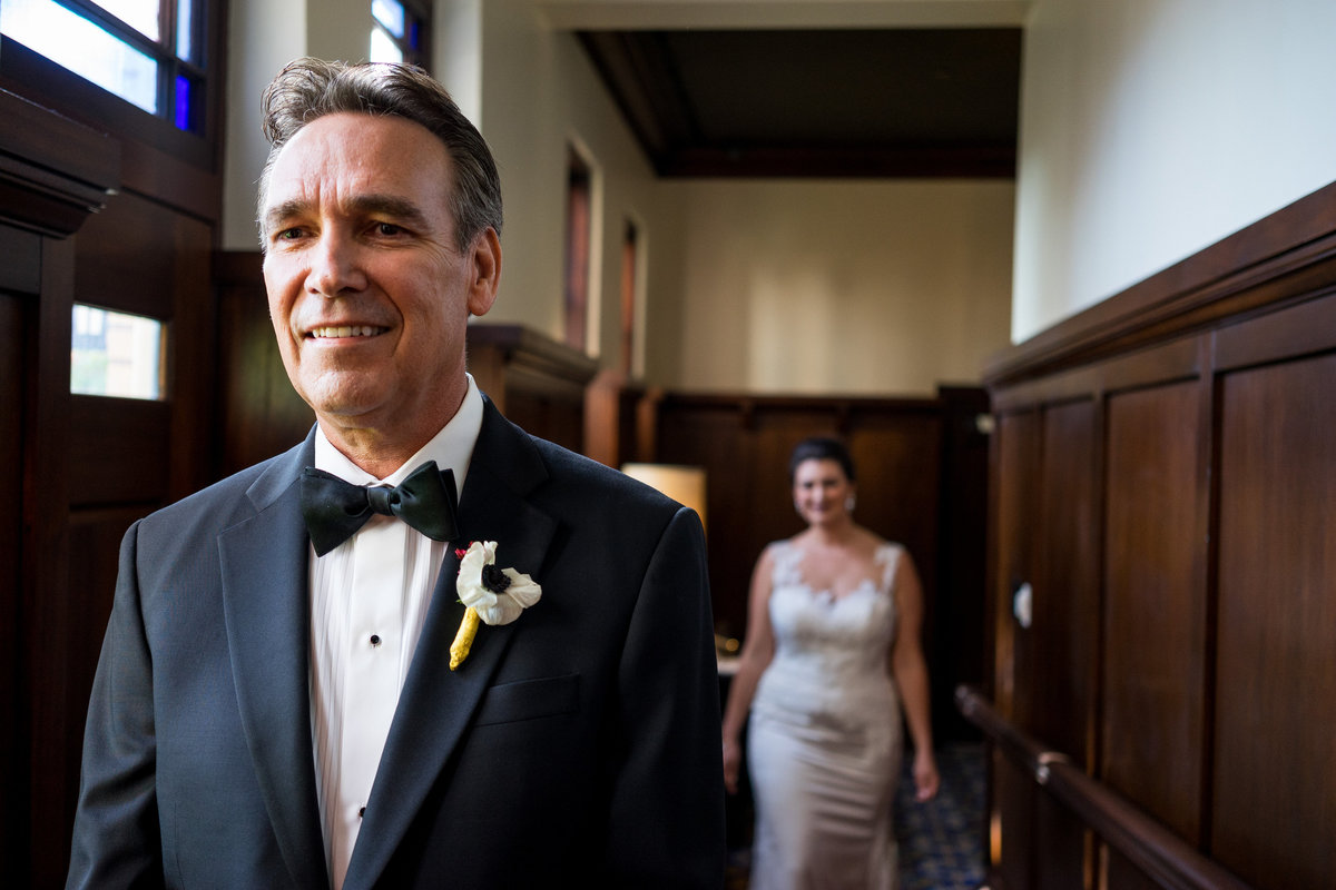 Bride walks up behind father of bride during first look with dad before wedding ceremony at Hotel Emma at The Historic Pearl
