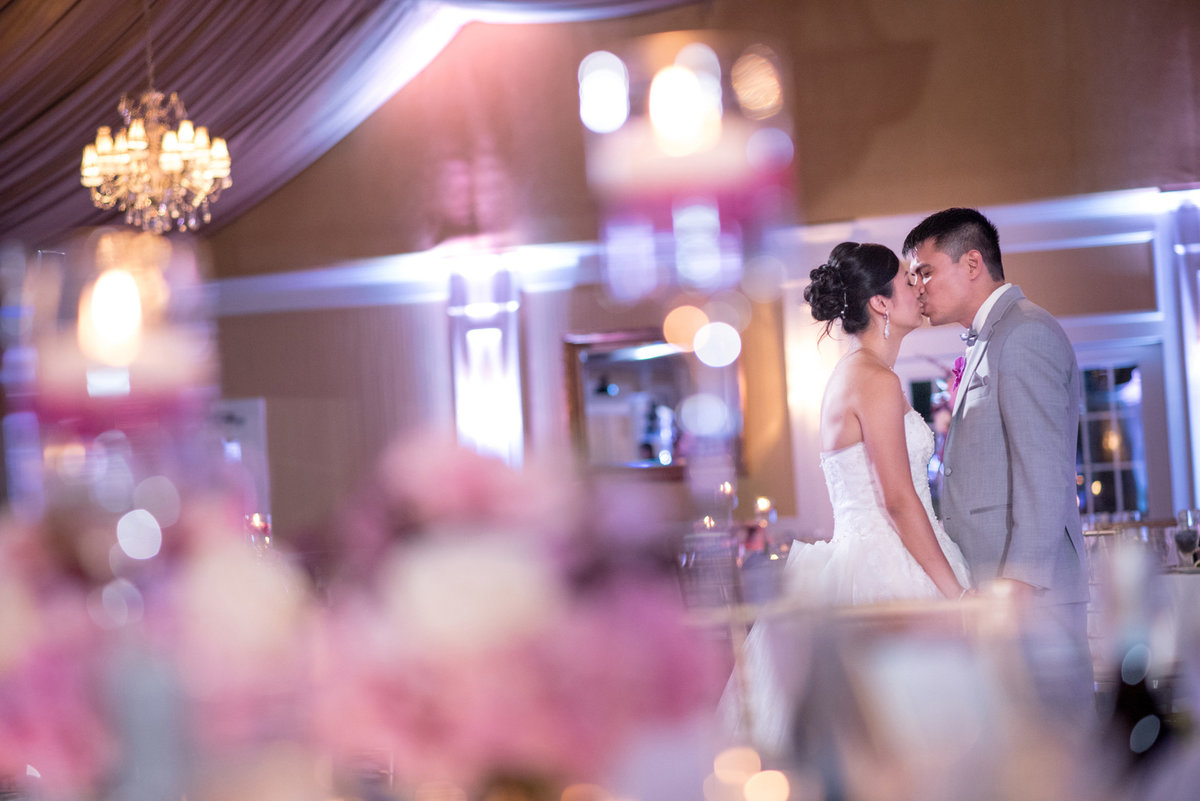 Bride and groom kissing at the ballroom of Bridgeview Yacht Club