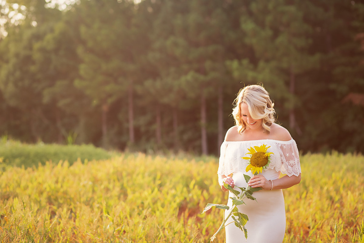 Expecting mom holding sunflower white maternity gown