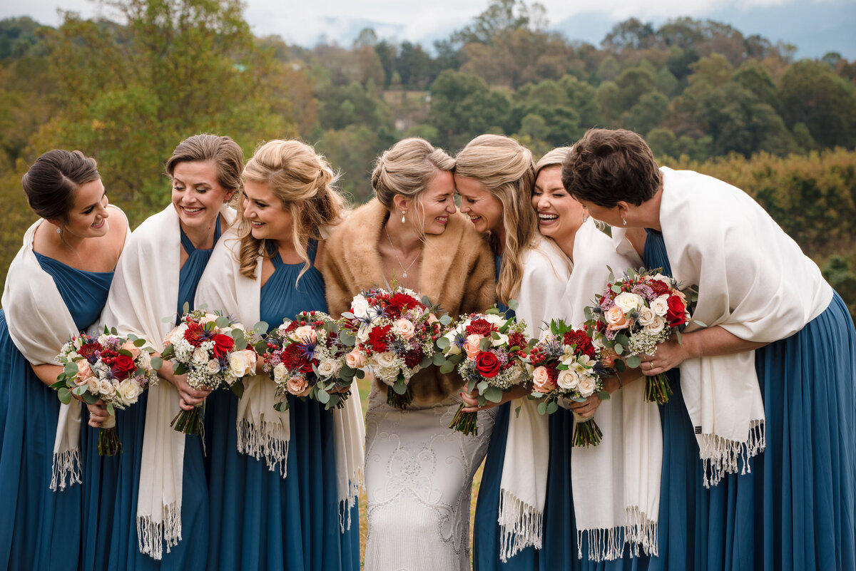Bride and bridesmaid laughing as a group