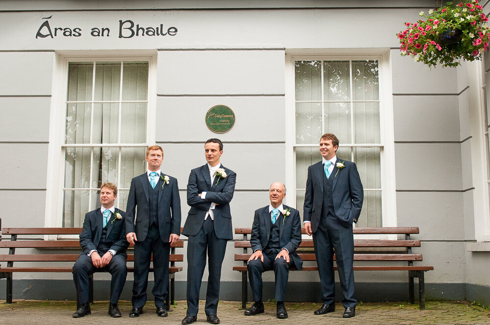 groom and his groomsmen wearing navy suits standing outside the town hall in Killarney