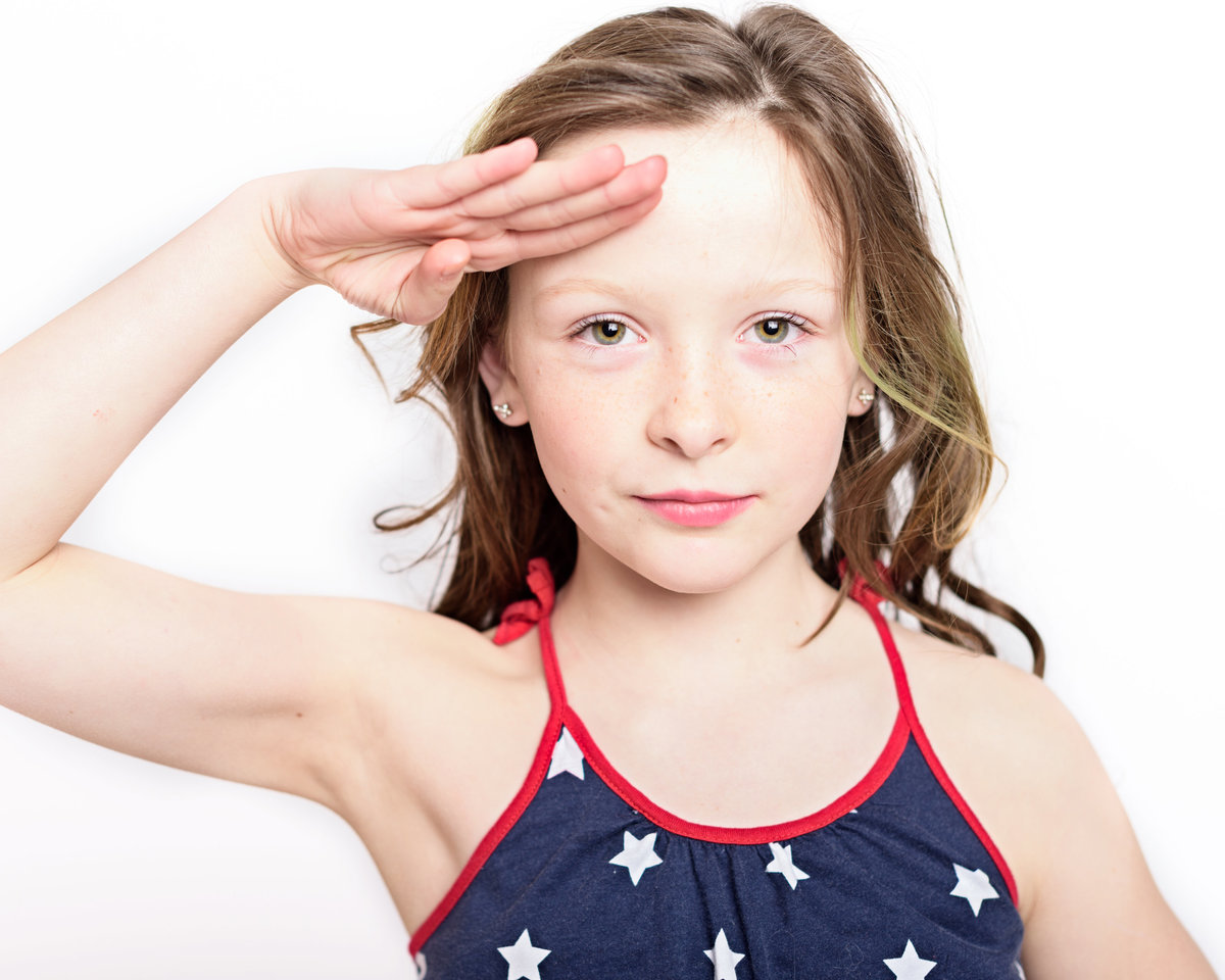 Patriotic photo of young girl saluting by Roslyn Family Photographer