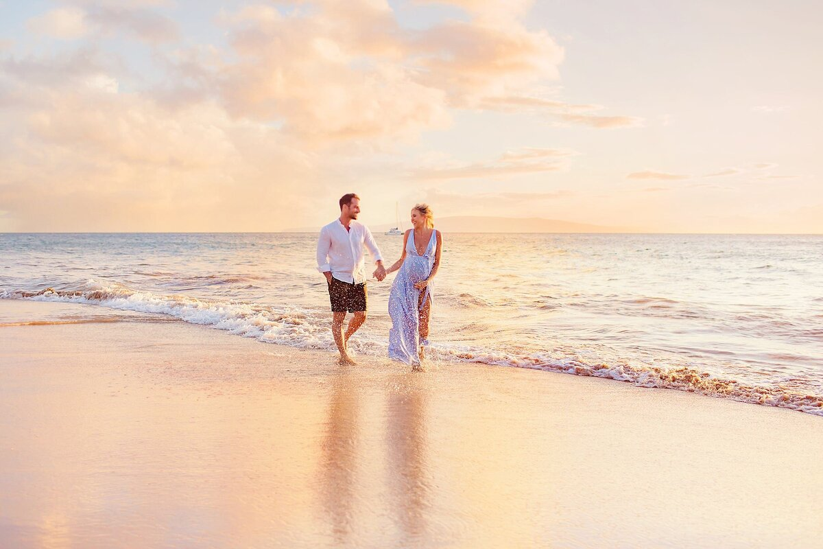 Couple splashes each other and walks on the beach during a Maui sunset