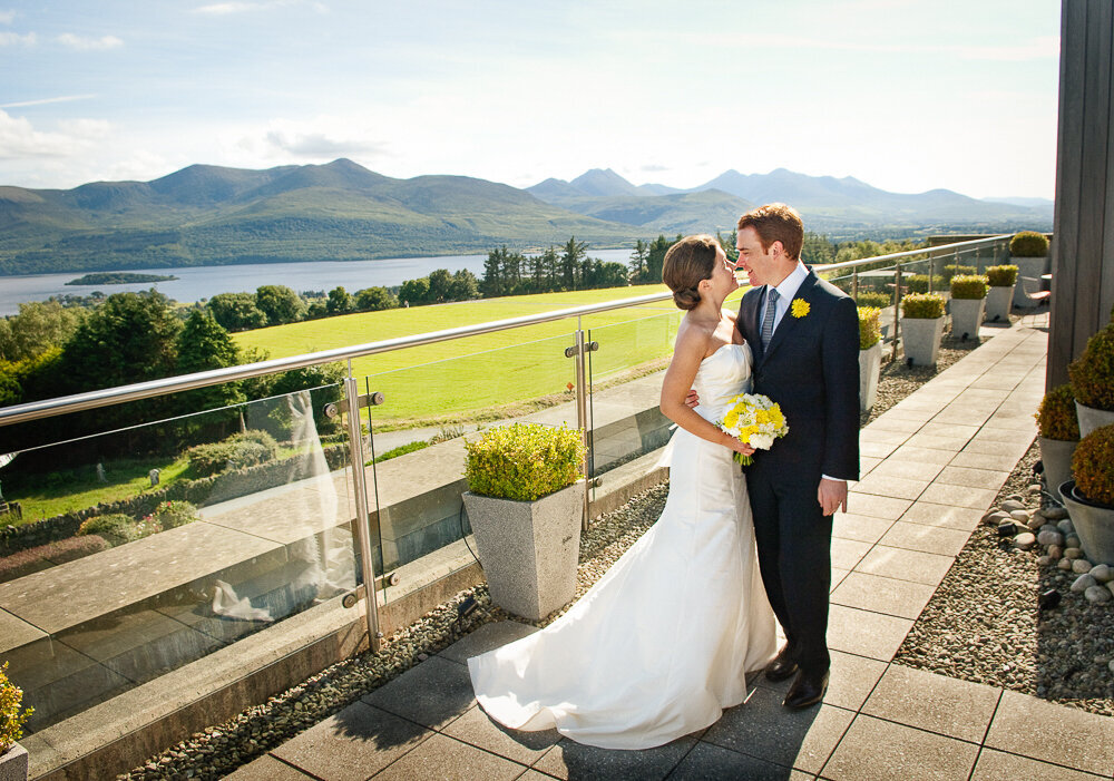 bride wearing a Greek style wedding dress, holding a yellow flower bouquet with her groom wearing a dark navy suit and yellow buttonhole, embracing on the terrace of the penthouse suite of the Aghadoe Hotel
