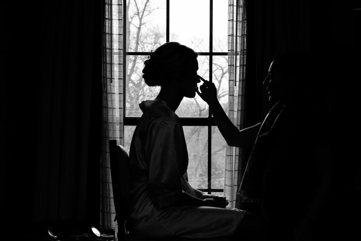 Bride getting makeup done in black and white at The Inn at Fox Hollow